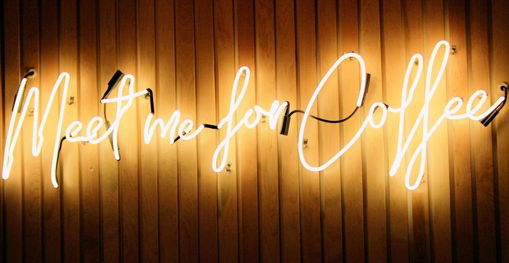 Beziehungen - das Miteinander zählt. Das Neonschild auf dem Foto zeigt: Meet me for coffee.