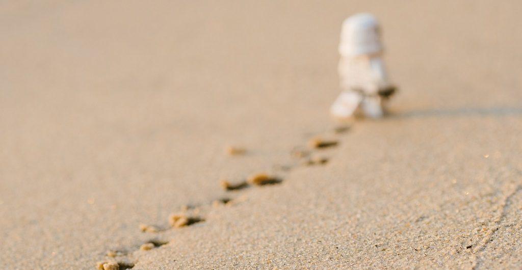 Stormtrooper-Figur geht weg und hinterlässt Spuren im Sand: Sinnbild für das Löschen vieler Instafollower