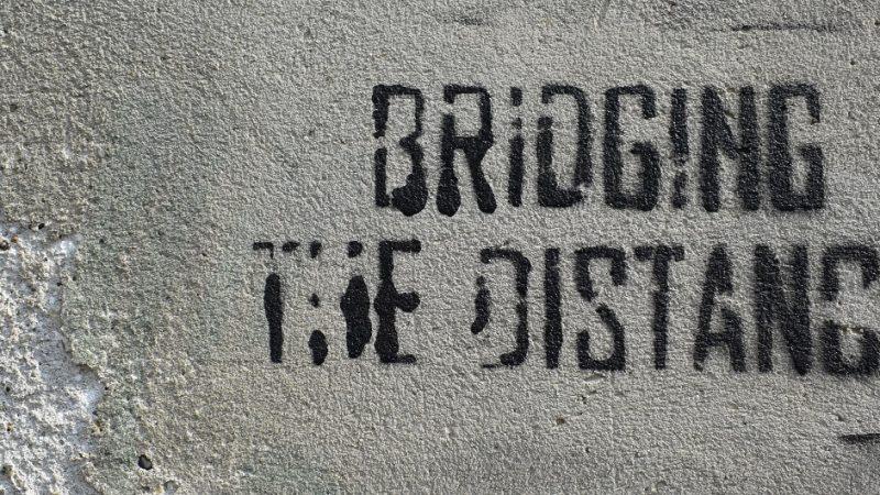 Zu sehen ist ein englischsprachiges Spraypaint: Bridging the Distance. Im Beitrag geht es darum, mit Gendern die gesamte Zielgruppe anzusprechen.