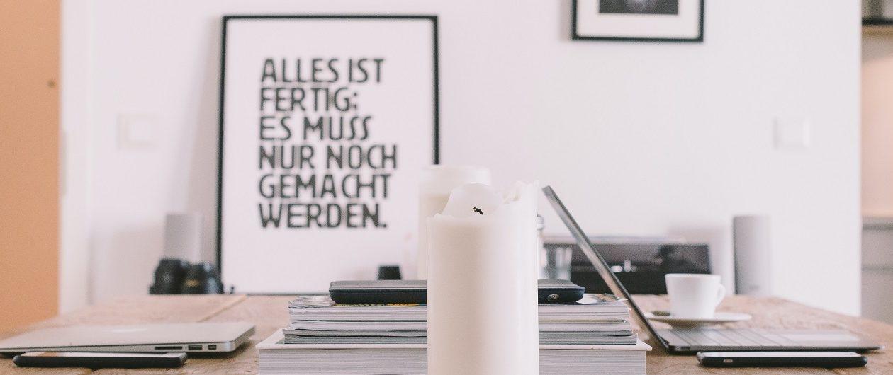 """Als Symbolbild für den Kommunikationsalltag bei FRAU RUPP ist ein Tisch zu sehen, mit Rechner, Notizen, einer Kerze und einem Schild """"Alles ist fertig: Es muss nur noch gemacht werden."""""""
